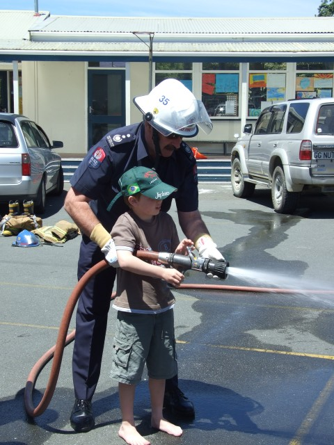 Chief Postlewaight assists a budding firefighter at the Police Christmas picnic.