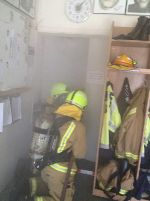 Probationary Firefighters Hintz-H and Aubrey practice searching a smoke filled building