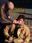 NZFS instructor Dave Watkins 'dresses' QFF Tim Manawaitai as a victim during first aid refresher course